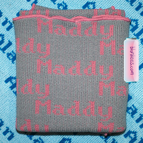 Personalized baby blanket knit with grey and dusty pink. The name Maddy is repeated all over the baby blanket.