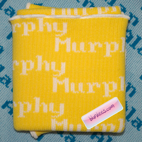 Personalized baby blanket knit with dark yellow and white with the name, Murphy, all over.